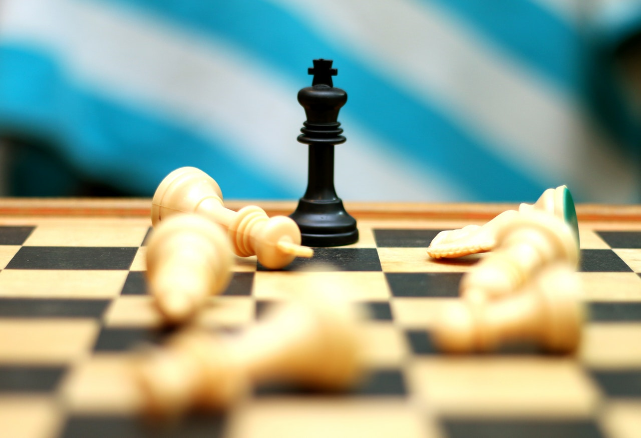 black queen chess piece standing on chess board, surrounded by fallen white pieces