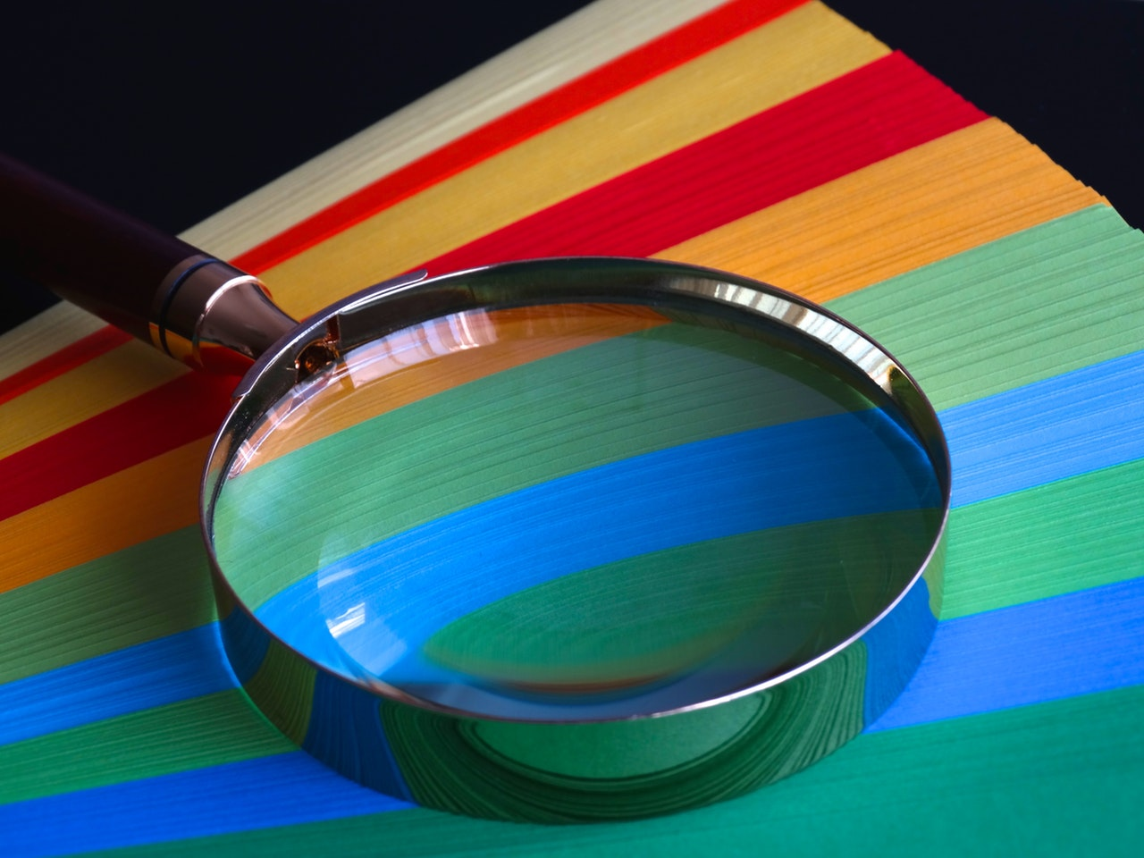 colourful folders under a magnifying glass