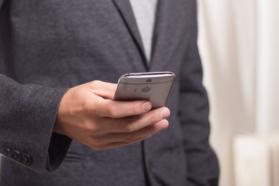 Man in Business Suit Holding Phone
