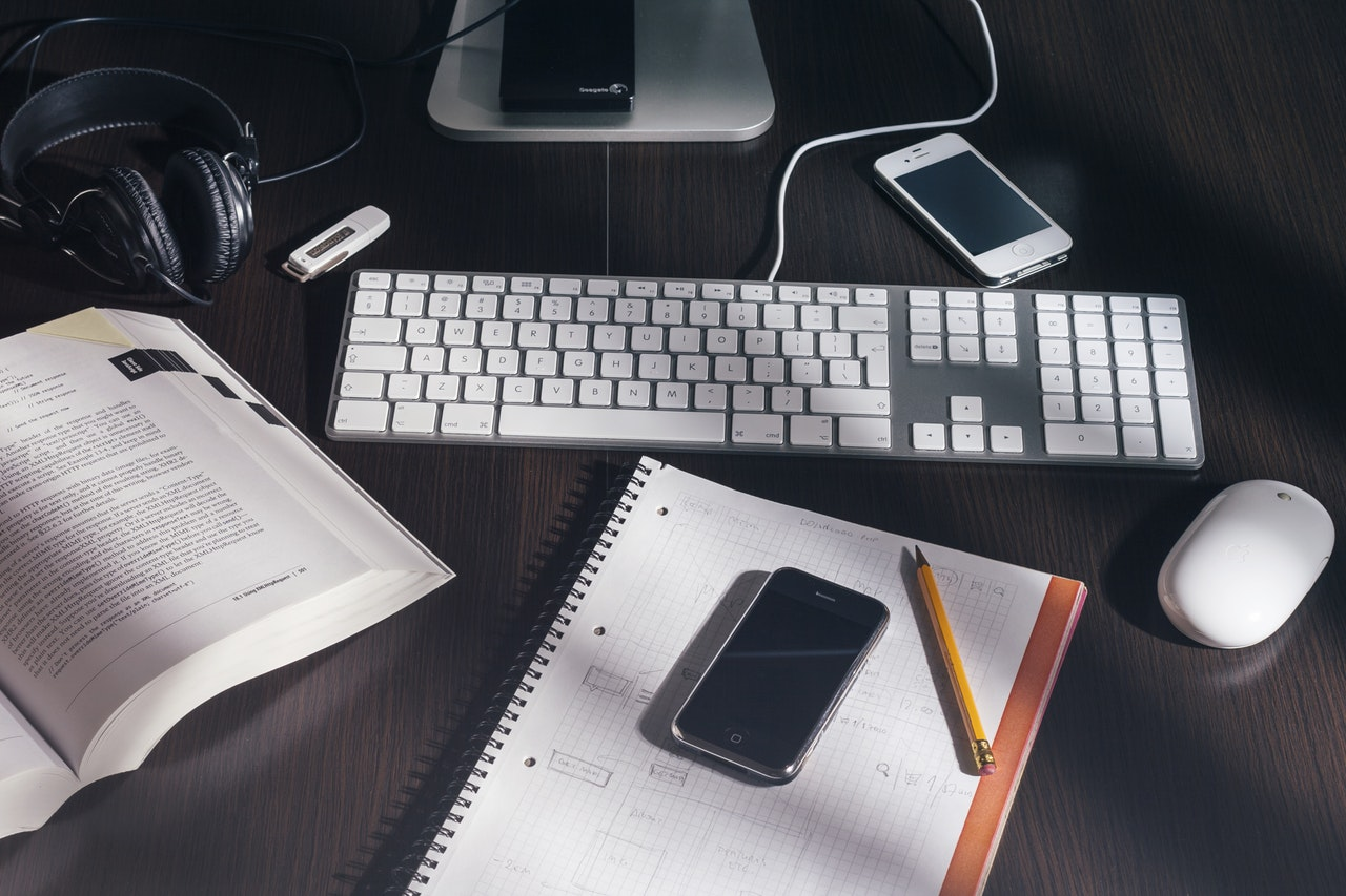work desk with notebook, phone and laptop