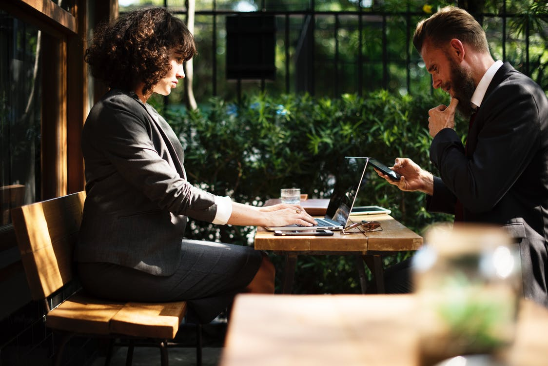 Meeting with man and woman looking at phone and laptop