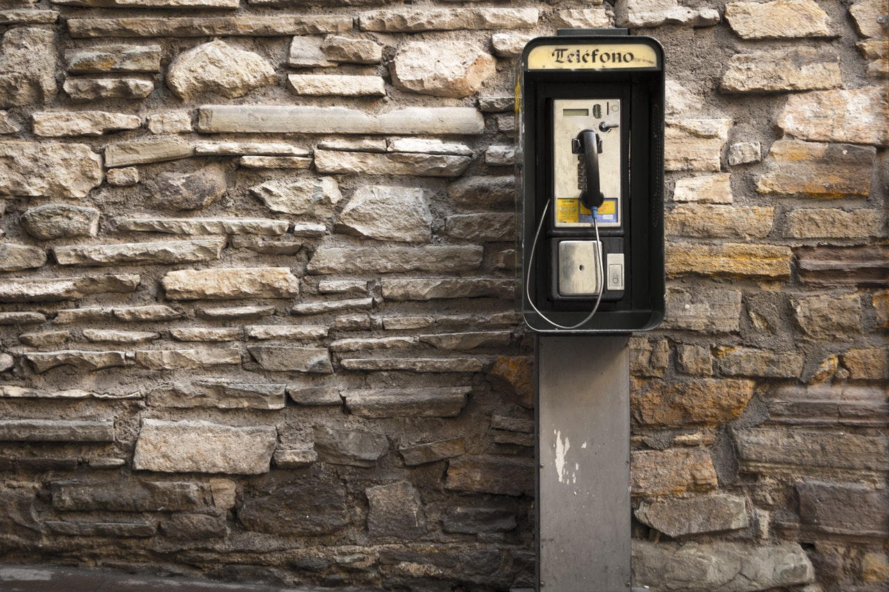 pay phone outside on grey brick background
