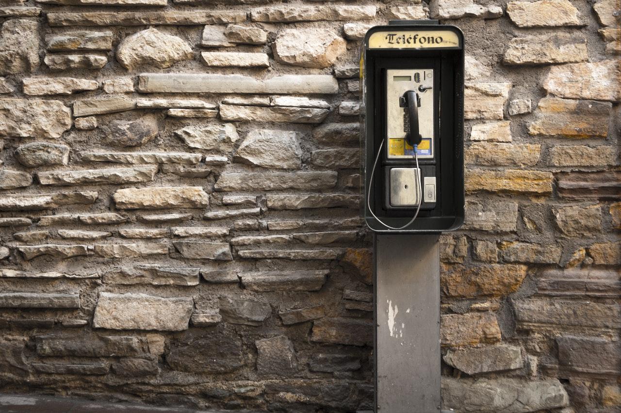 pay phone outside on grey brick background